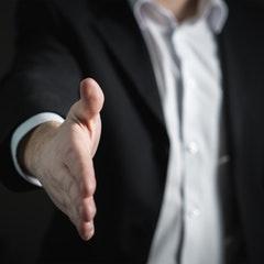 la foto mostra a una persona de peu que esten la mà per oferir-li a algú.
